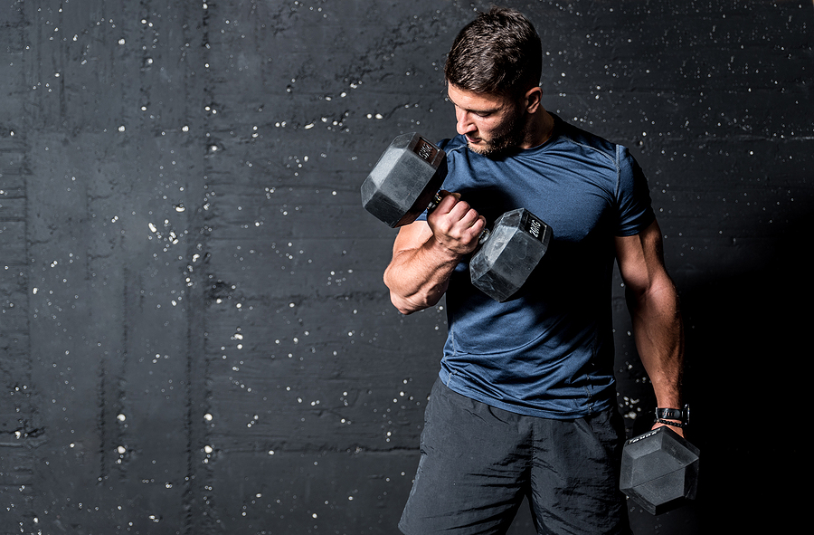 Man curling dumbbell with mind to muscle connection